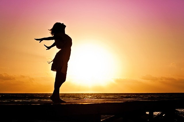 Woman enjoying a sunset at a beach